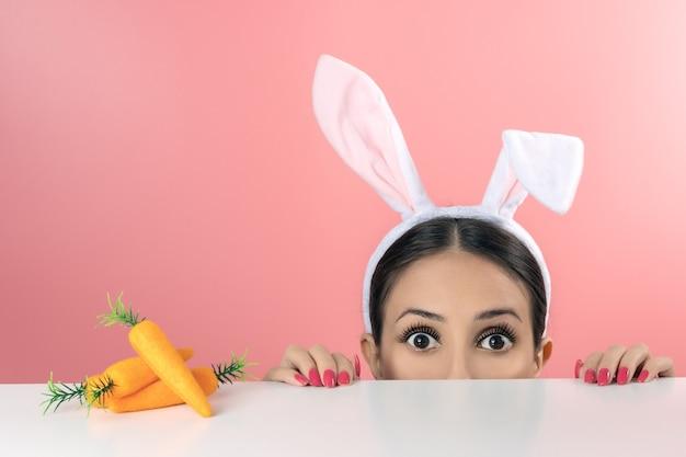 Piękna młoda kobieta z różowymi uszami królika i zabawkową marchewką na różowo.