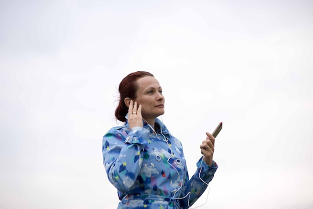 Piękna młoda kobieta z rude włosy, słuchanie muzyki w słuchawkach na białym tle