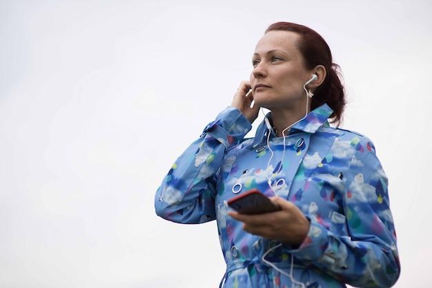 Piękna młoda kobieta z rude włosy, słuchanie muzyki w słuchawkach