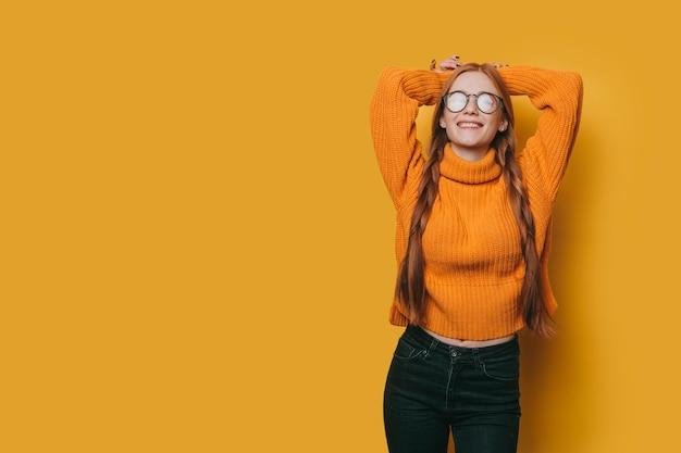 Piękna młoda kobieta z rudymi włosami i piegami ubrana na żółto patrząc na kamery, uśmiechając się, opierając się na żółtej ścianie studia.