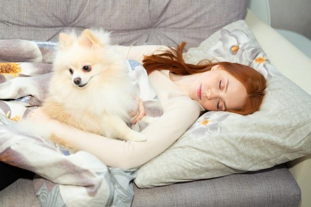 Piękna młoda kobieta z rudymi włosami śpi na łóżku pod kołdrą