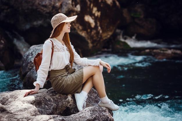 Piękna młoda kobieta z rudymi włosami, w kapeluszu iz plecakiem w pobliżu hałaśliwej rzeki w lesie.