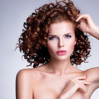 Piękna młoda kobieta z seksowny makijaż i stylową fryzurę pozowanie studio na szarym tle.