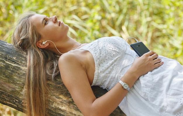 Piękna młoda kobieta z słuchawkami relaksujący na łonie natury, słucha muzyki za pomocą telefonu, chill out i koncepcja wypoczynku
