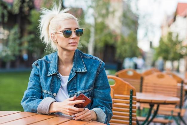 Piękna młoda kobieta z smartphone obsiadaniem przy kawiarnią outdoors