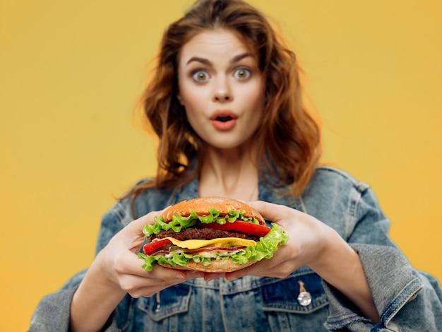 Piękna młoda kobieta z soczystym hamburgerem w dłoniach, kobieta je hamburgera