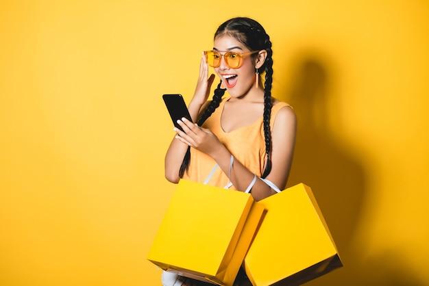 Piękna młoda kobieta z torba na zakupy używać jej mądrze telefon na żółtym tle.