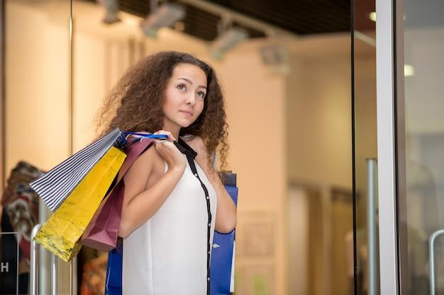 Piękna młoda kobieta z torba na zakupy w centrum handlowym