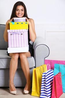 Piękna młoda kobieta z torbami na zakupy i pudełkami, siedząca na kanapie w pokoju