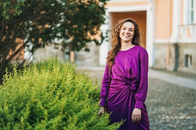 Piękna młoda kobieta z trzepotliwym włosy ubierającym w purpurowej sukni chodzi outdoors szeroki ono uśmiecha się. koncepcja szczęśliwych ludzi.
