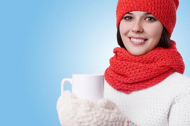 Piękna młoda kobieta z uroczym uśmiechem i jasnymi oczami, ubrana w ciepłe zimowe ubrania z dzianiny