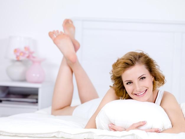 Piękna młoda kobieta z wesołym szczęśliwym uśmiechem, leżąc na łóżku - w pomieszczeniu