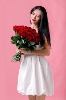 Piękna młoda kobieta z wielkim bukietem czerwonych róż