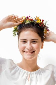 Piękna młoda kobieta z wieńcem kwiatowym w środku lata