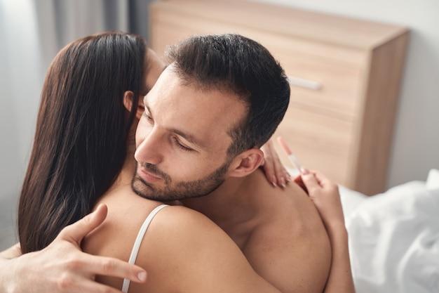 Piękna młoda kobieta z zamkniętymi oczami, obejmująca swojego ciemnowłosego kaukaskiego męża w sypialni