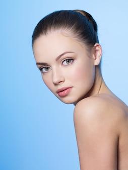Piękna młoda kobieta z zdrową czystą skórą na niebiesko