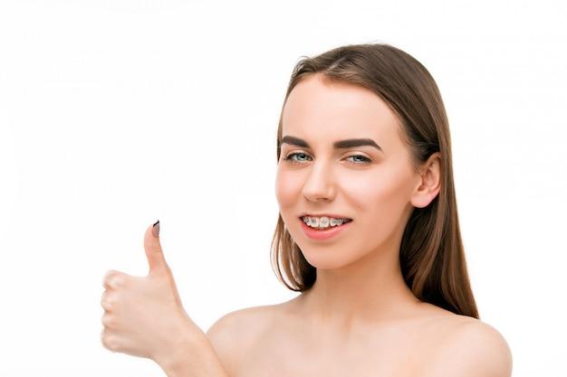 Piękna młoda kobieta z zębów szelkami