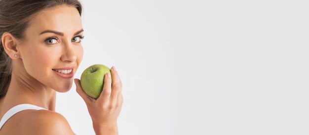 Piękna młoda kobieta z zielonym jabłkiem z bliska na białej ścianie