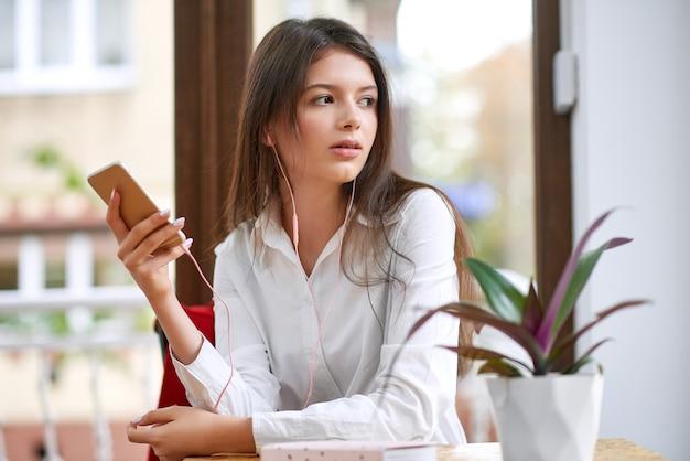 Piękna młoda kobieta za pomocą swojego inteligentnego telefonu, noszenie słuchawek