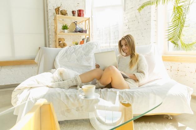 Piękna młoda kobieta za pomocą swojego laptopa, leżąc na kanapie w domu z ciepłym światłem słonecznym przez okno.
