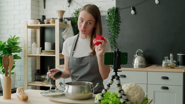 Piękna młoda kobieta za pomocą swojego smartfona kręci wideo-blog o pysznym i zdrowym jedzeniu w domowej kuchni