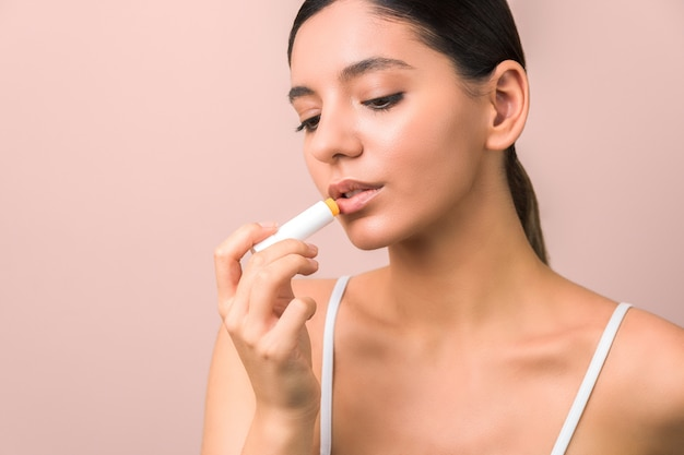 Piękna młoda kobieta za pomocą szminki do nawilżania ust. naturalne usta i ochronna szminka