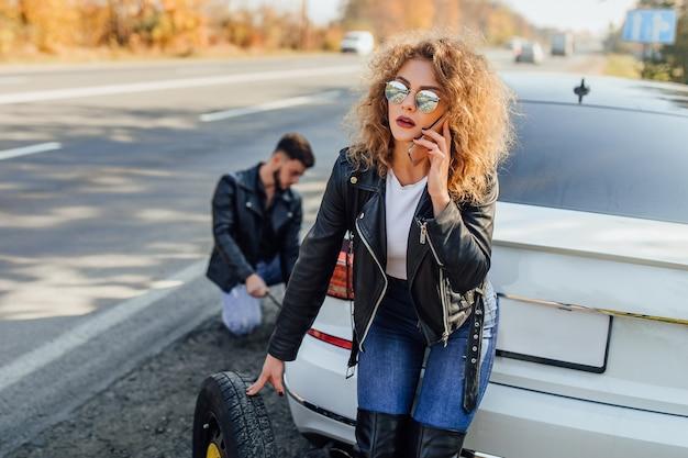 Piękna młoda kobieta za pomocą telefonu komórkowego wzywa pomoc do samochodu.