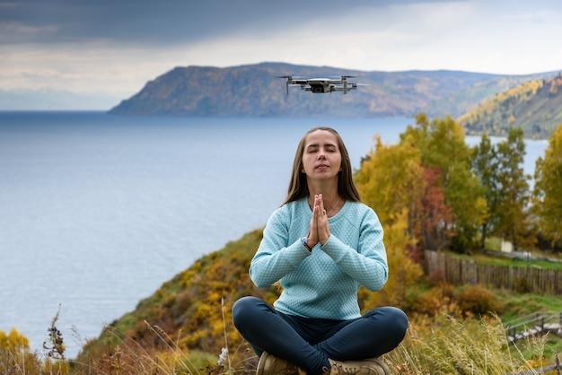 Piękna młoda kobieta zabawy z mini dronem na zewnątrz w pozie lotosu.
