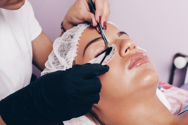 Piękna młoda kobieta zaczyna procedurę przedłużania rzęs. koncepcja kosmetyków i pielęgnacji ciała.