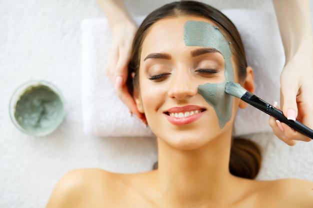 Piękna młoda kobieta zaczyna zabieg na twarz w salonie piękności