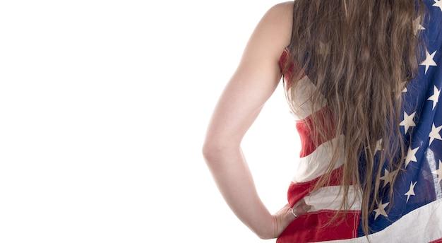 Piękna młoda kobieta zawinięta w amerykańską flagę na białym tle