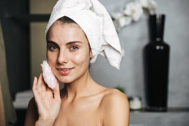 Piękna młoda kobieta zawinięta w ręcznik stojący w łazience