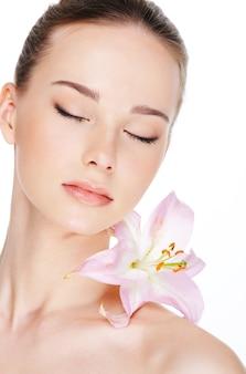 Piękna młoda kobieta ze skórą zdrowia i kwiatem na ramieniu