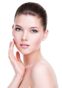 Piękna młoda kobieta ze świeżą, czystą skórą, która dotyka jej twarzy ręką - na białym tle.