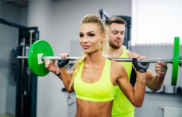 Piękna młoda kobieta ze swoim osobistym trenerem na siłowni omawia swoje postępy w schowku trzymanym przez mężczyznę. zdrowy tryb życia