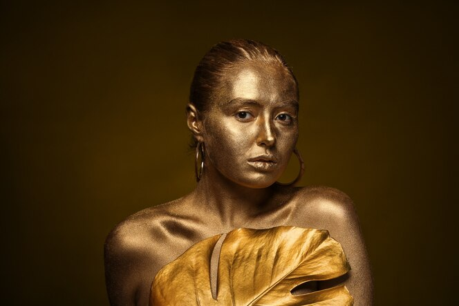 Piękna młoda kobieta ze złotą farbą na ciele i tropikalnym liściem na ciemnej powierzchni