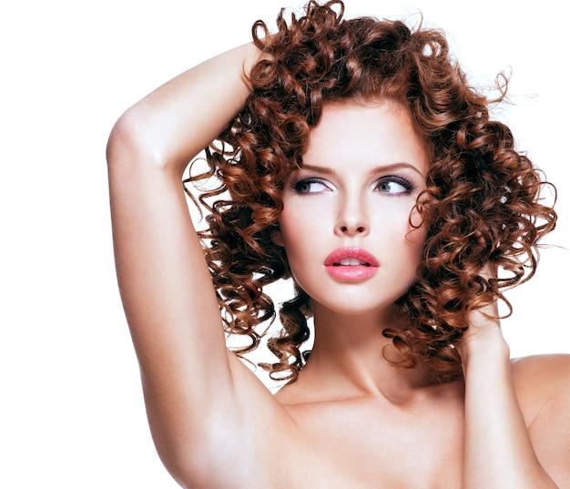Piękna młoda kobieta zmysłowa dotykając jej włosów rękami. piękna twarz z kręconymi fryzurami, na białym tle.
