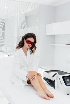 Piękna młoda kobieta zostanie poddana depilacji laserowej przy użyciu nowoczesnego sprzętu
