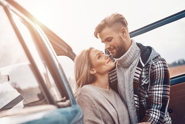 Piękna młoda kochająca para, która łączy się i patrzy na siebie, stojąc w pobliżu minivana na zewnątrz