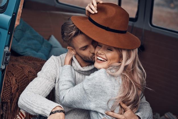 Piękna młoda kochająca para obejmująca się i uśmiechająca się podczas spędzania czasu w swoim minivanie