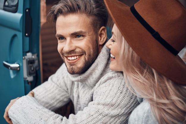 Piękna młoda kochająca się para, która łączy się i uśmiecha, spędzając czas w swoim minivanie