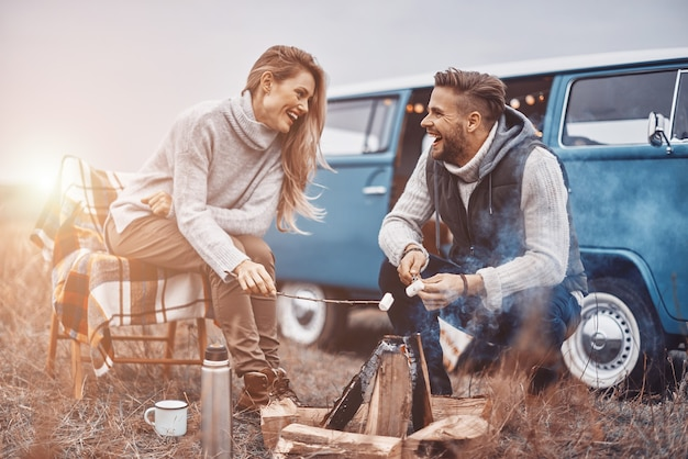 Piękna młoda kochająca się para urządza piknik przy ognisku, siedząc w pobliżu swojego retro minivana