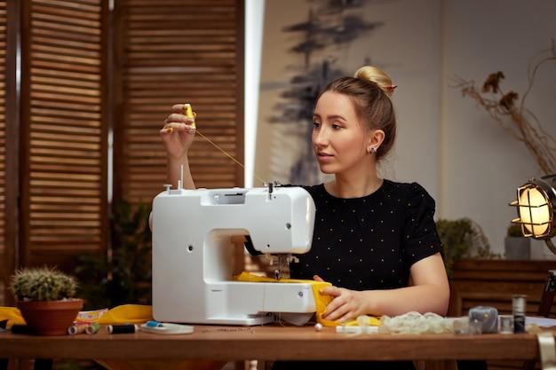 Piękna młoda krawcowa pracuje na maszynie do szycia