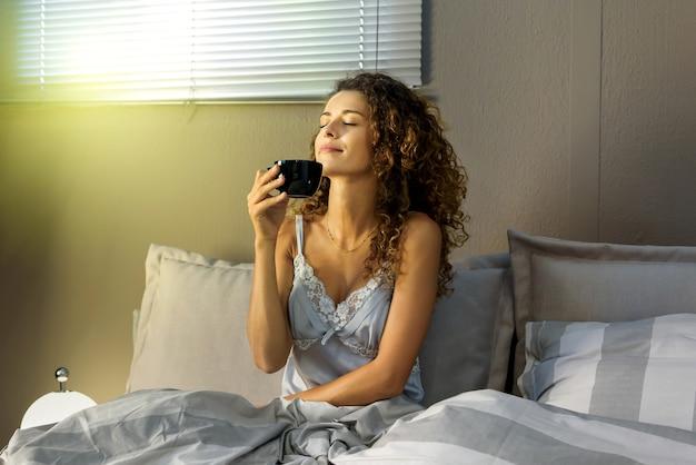 Piękna młoda kręcona kobieta w piżamie pachnie kawą w łóżku