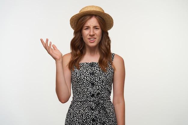 Piękna młoda kręcona kobieta z rudymi włosami wyglądająca z zaskoczeniem, podnosząca dłoń ze zdziwioną twarzą, ubrana w romantyczną sukienkę i kapelusz, na białym tle