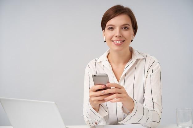 Piękna młoda krótkowłosa brunetka kobieta z naturalnym makijażem, uśmiechnięta przyjemnie i trzymająca w rękach telefon komórkowy, pozująca na biało w pasiastej koszuli