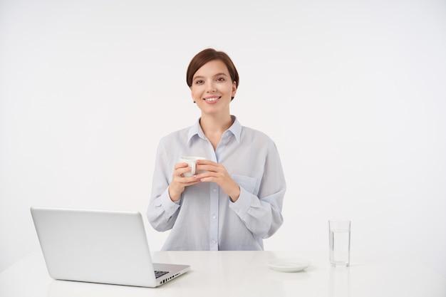 Piękna młoda krótkowłosa brunetka kobieta z naturalnym makijażem, wyglądająca pozytywnie z uroczym uśmiechem, trzymająca filiżankę herbaty w uniesionych rękach, odizolowana na białym