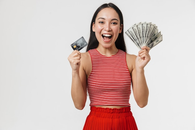 Piękna młoda ładna azjatycka podekscytowana kobieta pozowanie na białym tle nad białą ścianą, trzymając kartę kredytową i pieniądze.