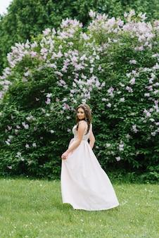 Piękna młoda ładna dziewczyna o luźnych długich włosach stoi w pobliżu kwitnącego bzu w długiej jasnoróżowej sukience. spogląda wstecz i idzie naprzód szczęśliwa