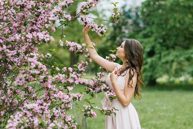Piękna młoda ładna dziewczyna o luźnych długich włosach stoi w pobliżu kwitnącego wiosennego krzaka weigela z różowymi kwiatami. dotyka ręką gałęzi. szczęśliwa pora roku
